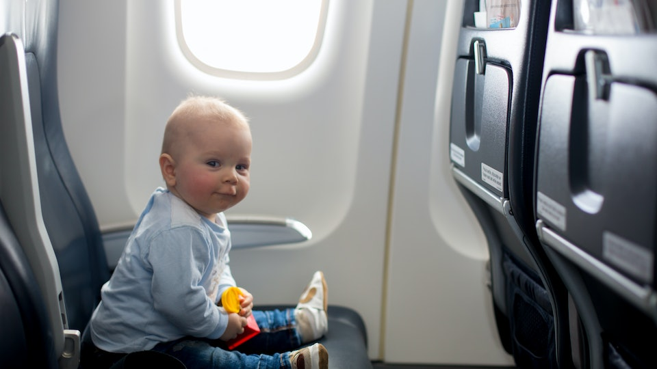 Cute baby boy, playing with toys on board of aircraft, traveling on vacation with parents and siblings