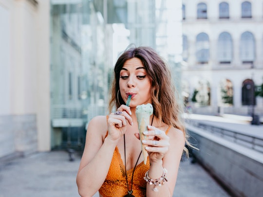 Beautiful young caucasian woman eating mint ice cream at the city street on a sunny day. Happy face smiling. Urban and summer lifestyle