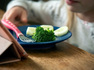 Child little girl eats broccoli and cucumber. Concept, healthy eating.