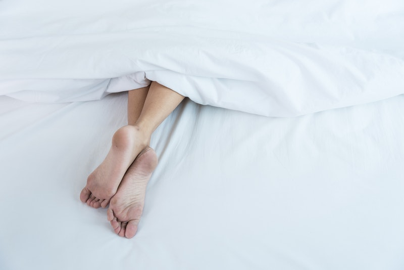 Under white blanket covers with feet showing on bed at home