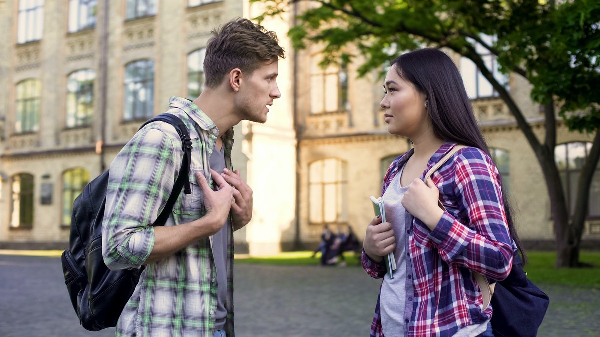 Emotional male student talking with ex-girlfriend near university, relationship