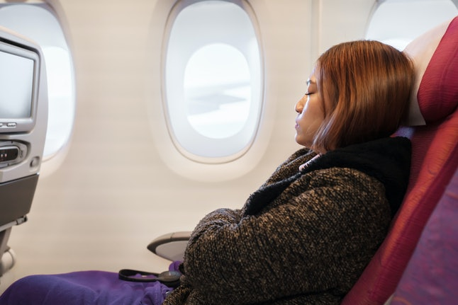 woman sleeping in an airplane in flight time.