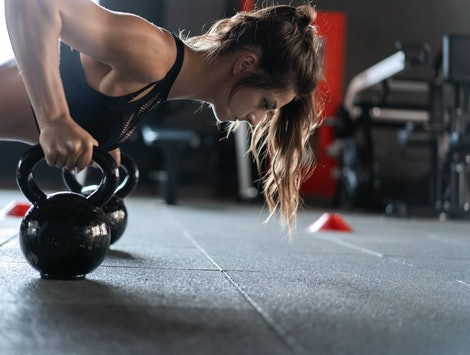 Sportive woman doing push-ups in the gym using kettlebells