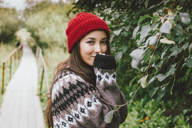 Beautiful carefree long hair asian girl in red hat and knitted nordic sweater in autumn nature park, travel adventure lifestyle