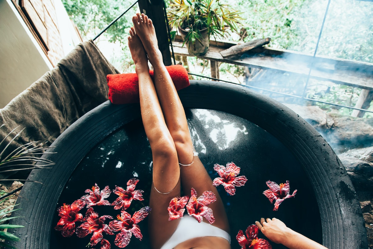 Woman relaxing in round outdoor bath with tropical flowers. Organic skin care in kawa hot bath in lu...