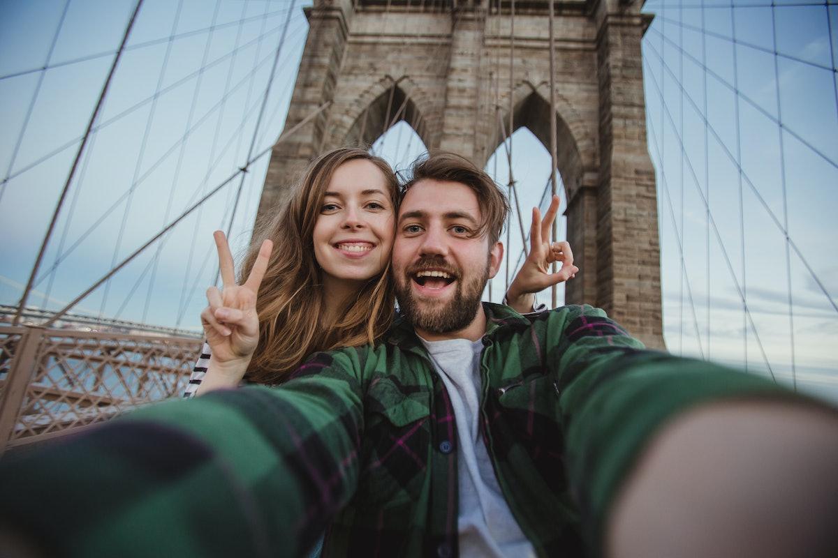 Beautiful happy couple taking selfie self-portrait on Brooklyn Bridge, New York. Hipster tourists ha...