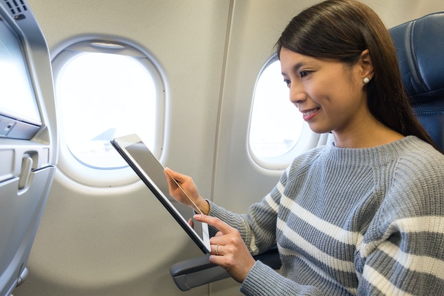 Woman use of tablet inside airplane