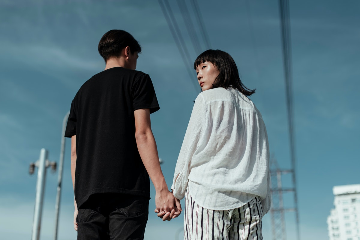 Rear view of millennial asian couple holding hands walking together on urban street against clear blue sky - half body