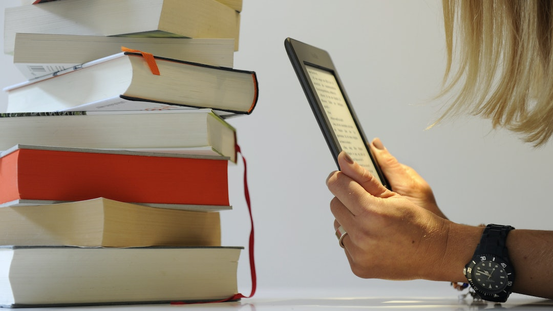 Young woman reading an e-book on a Kindle