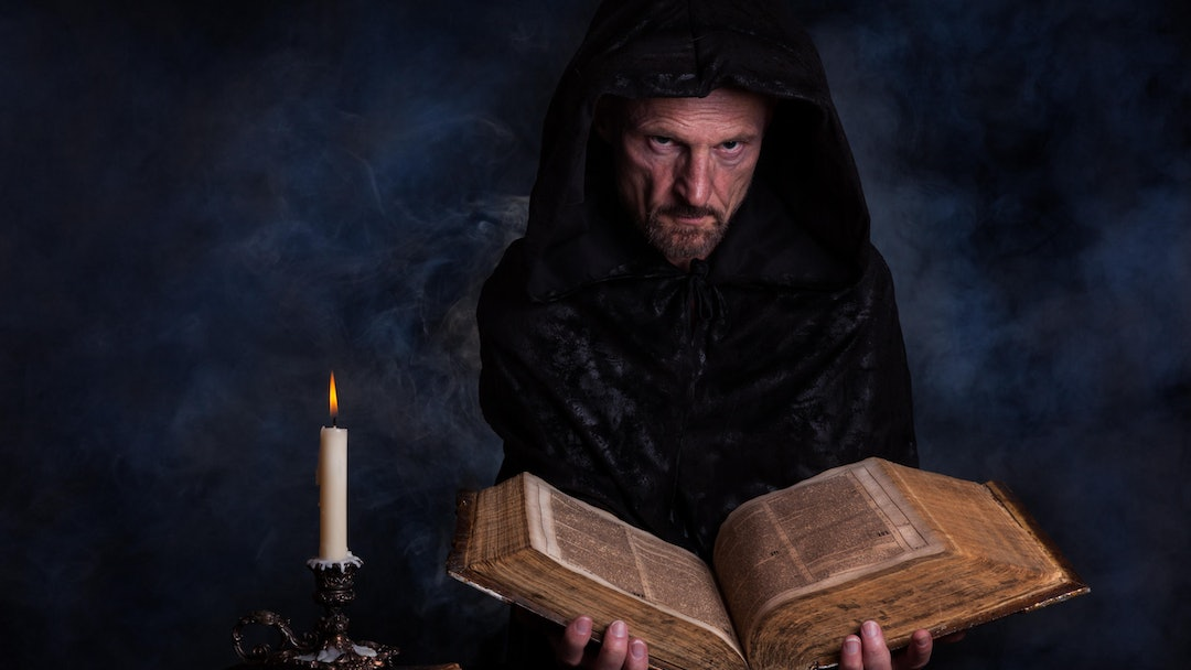 MODEL RELEASED Man, with a black hooded coat, holding an old book in his hands, in front a burning candle, Germany