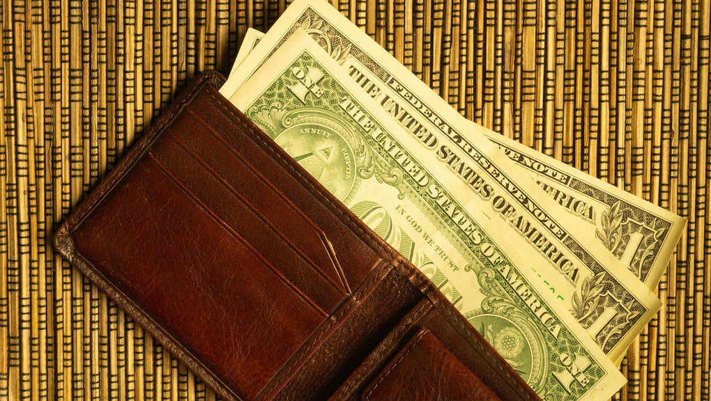 Dollars in a wallet on a wooden bamboo background. money on the table. finance background