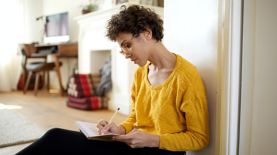 Portrait of young african american woman sitting on floor writing ideas into book