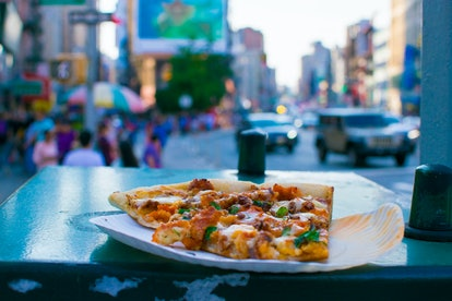A slice of pizza in the middle of busy China Town, New York City