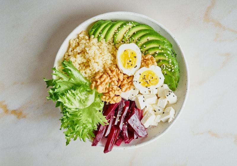 Buddha bowl, balanced food, vegetarian menu. Grey marble table, top view. Eggs, avocado, salad lettu...
