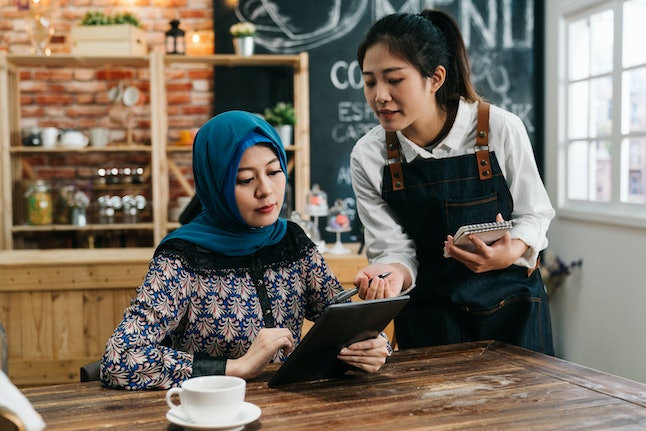 Young Asian waitress advising islam woman client to choose new snack from menu on mobile pad in restaurant. girl coffee shop staff taking order of muslim lady customer in cafe bar for lunch meal.