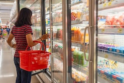 A girl with a basket takes frozen foods from the supermarket's refrigerator. The girl chooses goods ...