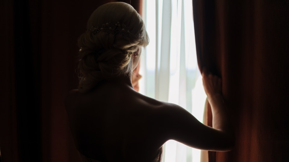 The bride looks out the window, opening the curtain. waiting for the groom. the view from the back