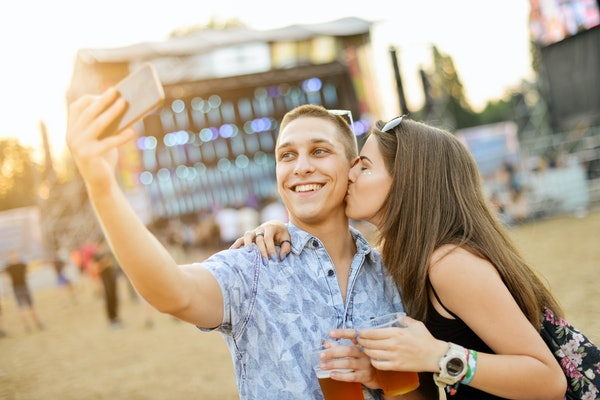 Couple taking selfie and having fun at music festival