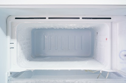 empty freezer of a refrigerator - Ice buildup on the inside of a freezer walls.
