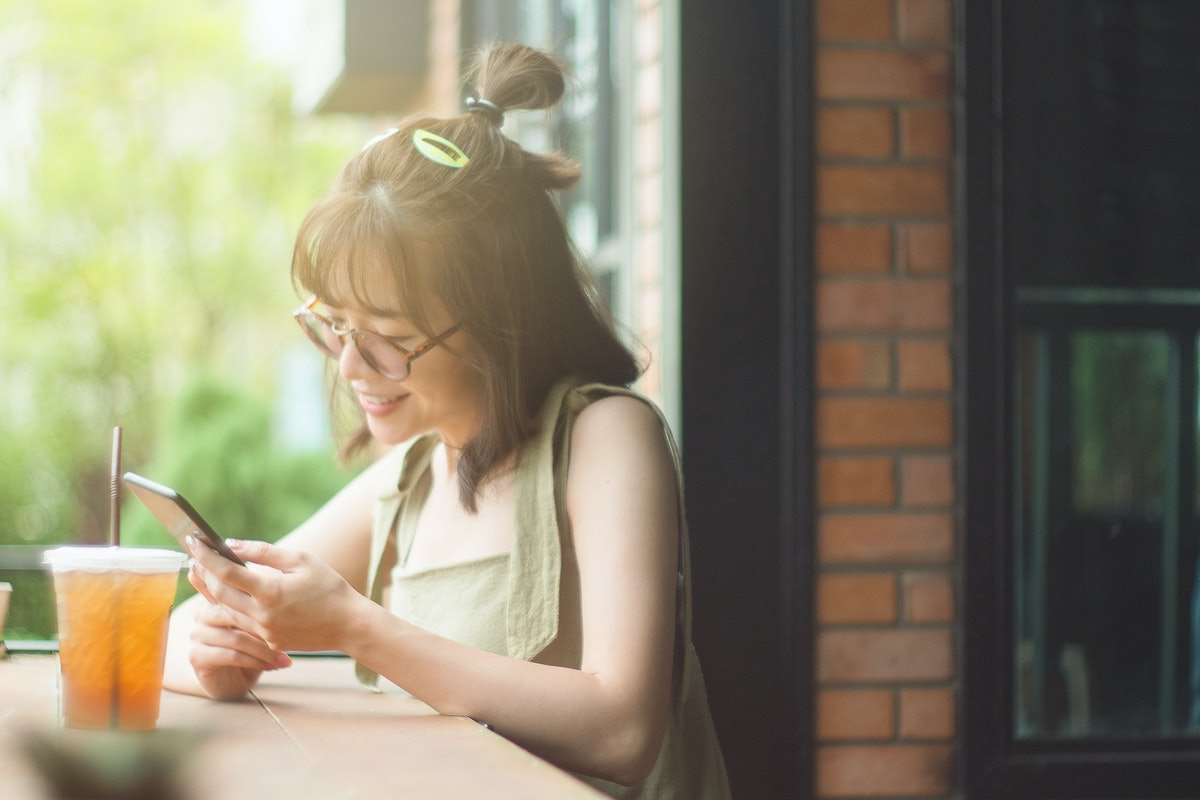Portrait of cute asian teen woman using smartphone at coffee cafe. texting with someone. reading ple...