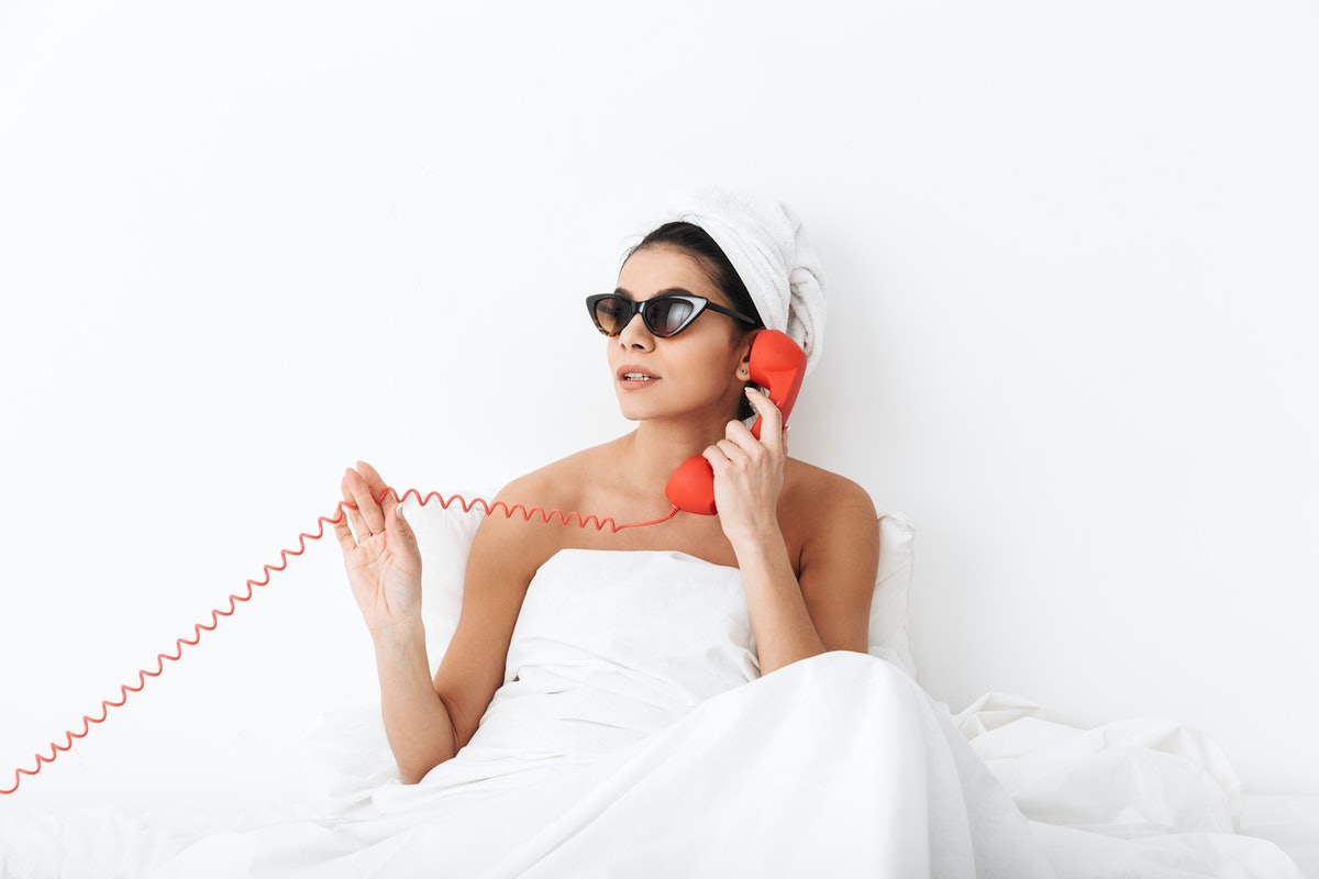 Image of a beautiful emotional woman with towel on head lies in bed under blanket isolated over white wall background wearing sunglasses talking by phone.