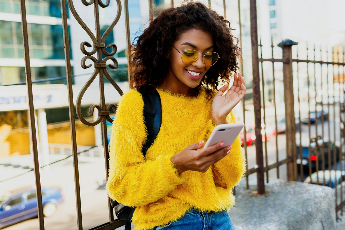 Outdoor image of young attractive American student woman with stylish hairs using mobile phone and sitting on bridge in modern district. Yellow glasses and pullover.