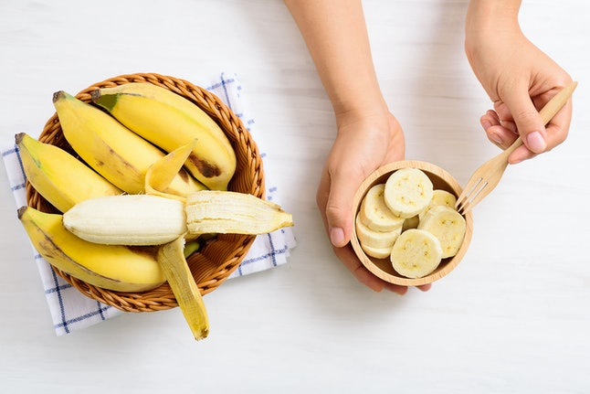 Hand holding fork for eating sliced banana in a bowl and peeled banana in a basket, top view