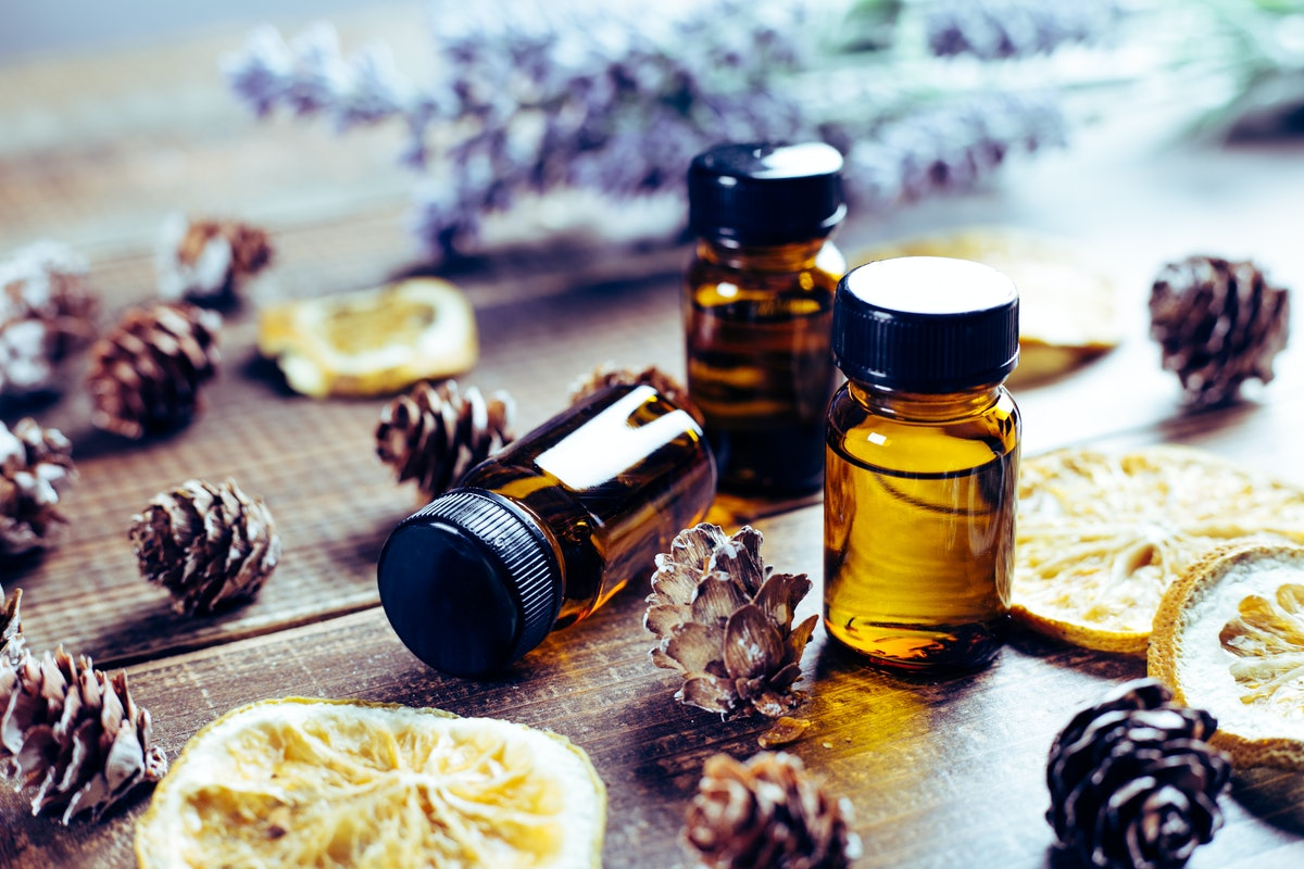 Bottles filled with essential oils sit on a table with lemons and pinecones at a class.