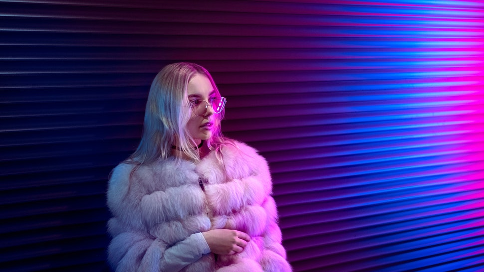 Teen hipster girl in stylish glasses and fur standing on purple street neon light wall background, female teenager fashion model pretty young woman looking at night club city light glow, back to 80s