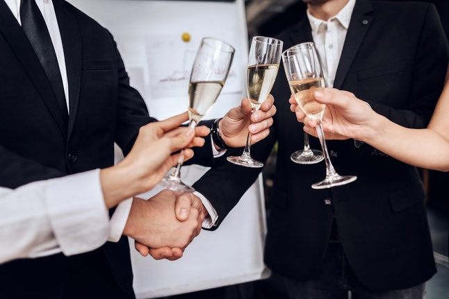 Young people in suits wear alcoholic drinks after a business meeting. In their hands they hold glasses with champagne.