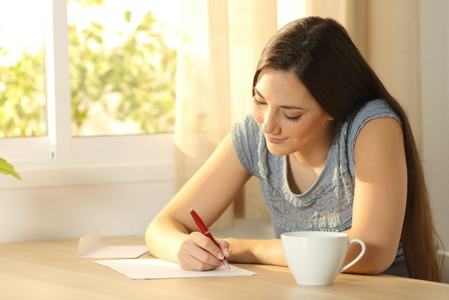 Happy girl writing a letter on a table at home