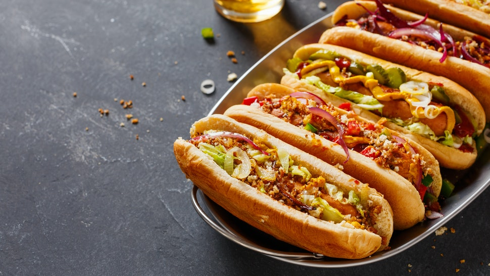 Hot dogs fully loaded with assorted toppings on a tray. Food background with copy space.