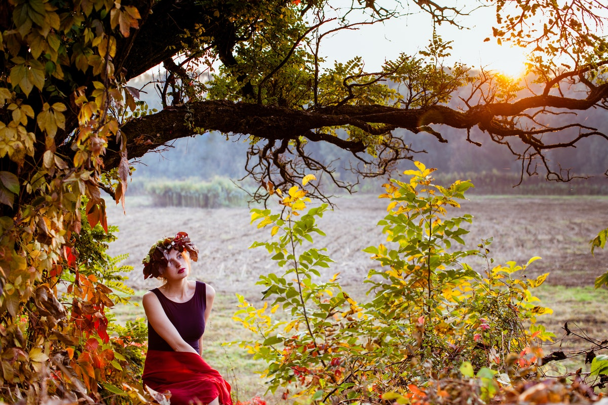 Sensual woman under the autumnal tree on sunset