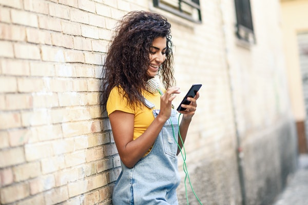 Young North African woman texting with her smart phone outdoors. Smiling Arab girl in casual clothes with black curly hairstyle.