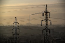 Smoke rises from the chimney of the incineration plant with high voltage lines in the foreground dur...