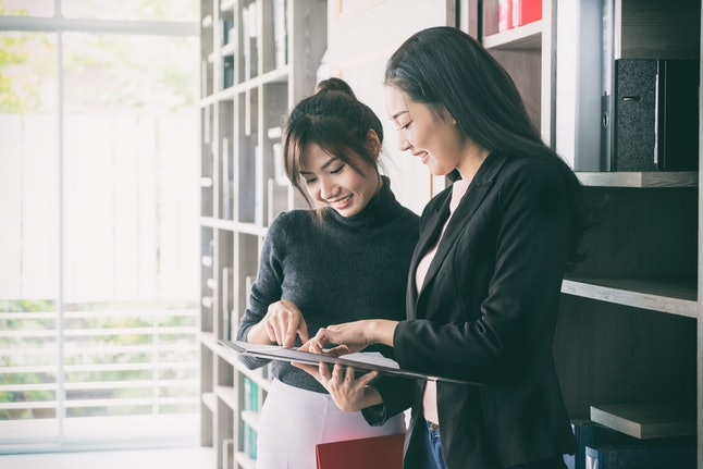 Two Asian businesswoman collegues standing next to each other in an office. They businesswoman talking about report in files.