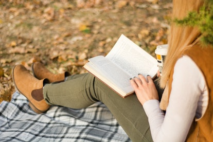 Young girl reading and holding book on legs at retro blanket at park on autumn day. Fall leaf blurred in background. Woman wears autumn clothes. Close up, selective focus