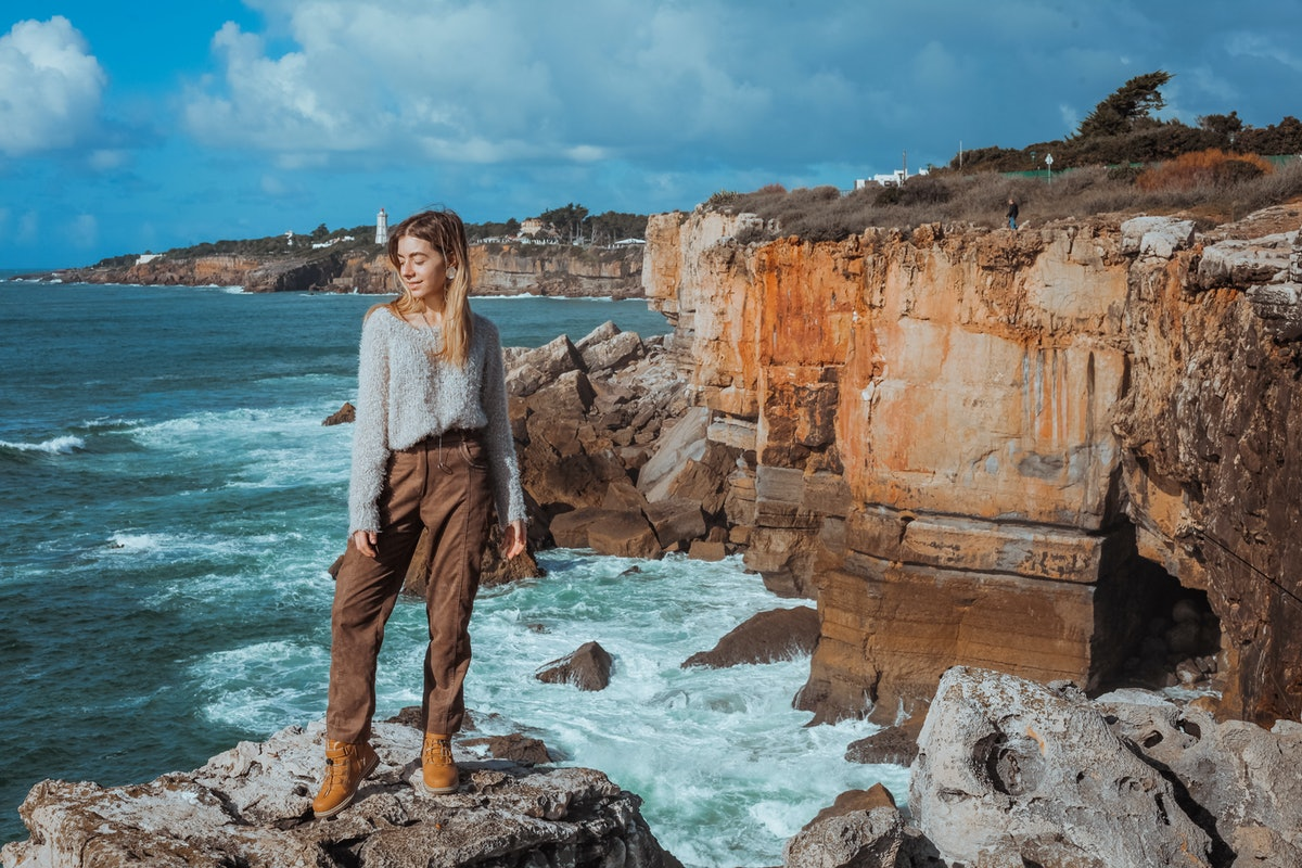 Beautiful woman posing on rocky cliff at Cascais , Portugal