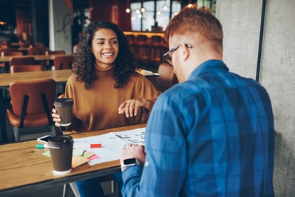 Smiling african american girl having fun during meeting with back view friend on break , cheerful young woman share successful ideas  and good news with male colleague talking with coffee in cafe