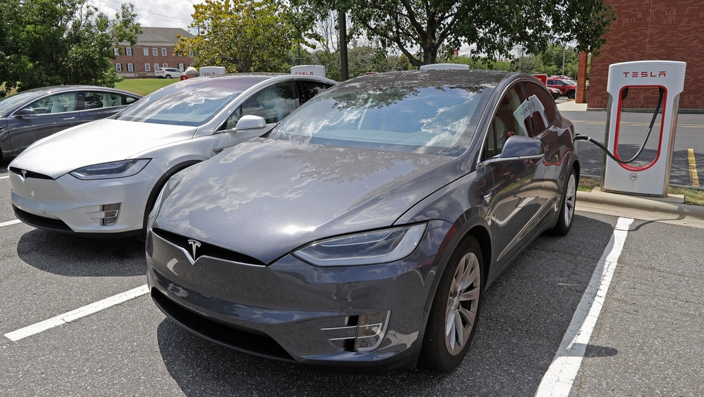 In this July 19, 2019, photo people wait inside their Tesla vehicles at a Tesla Supercharger site in Charlotte, N.C. Tesla, Inc. reports earning on