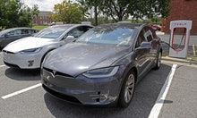 In this July 19, 2019, photo people wait inside their Tesla vehicles at a Tesla Supercharger site in...