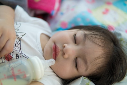 Adorable Asian baby sleeping and drinking milk.