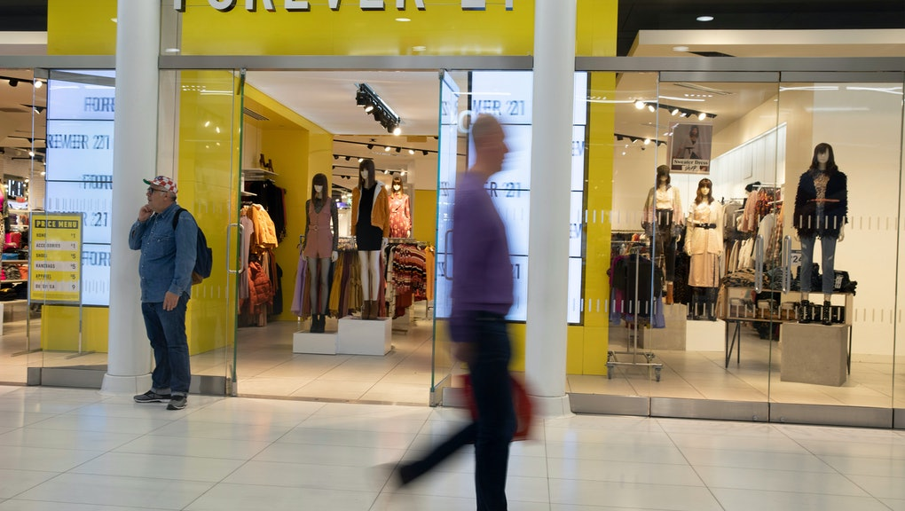 People walk in front of a Forever 21 clothing store, in New York. Low-price fashion chain Forever 21, a one-time hot destination for teen shoppers that fell victim to its own rapid expansion and changing consumer tastes, has filed for Chapter 11 bankruptcy protection