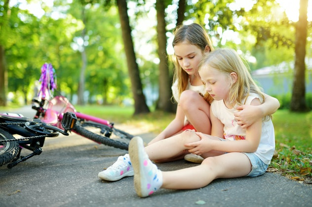 Adorable girl comforting her little sister after she fell off her bike at summer park. Child getting...