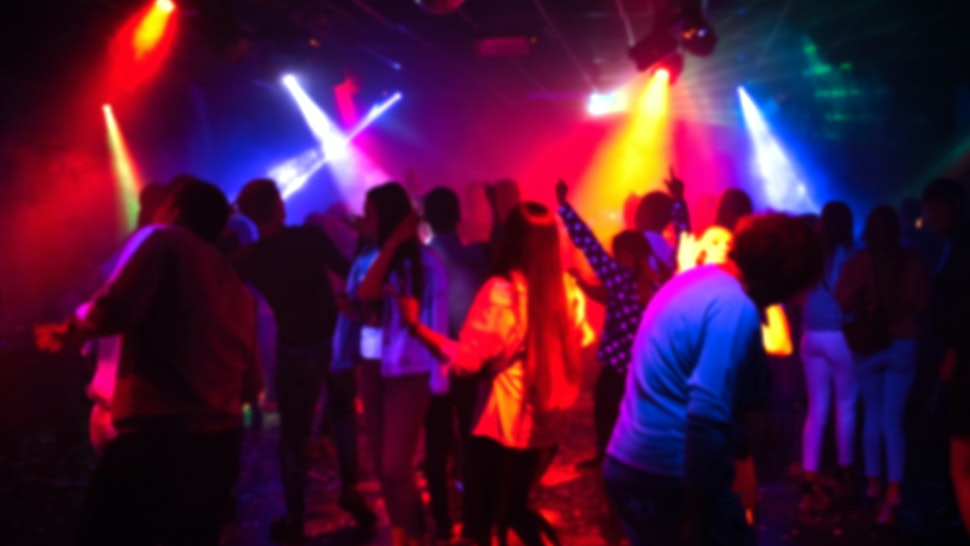 blurred silhouettes of a group of people dancing in a nightclub on the dance floor under colorful spotlights out of focus