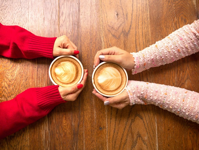 Two female hands holding cup of coffee a wooden vintage table in a coffeeshop, friend drink coffee
