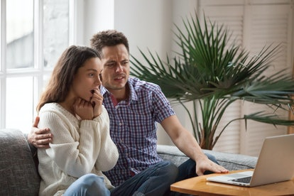 Scared man embracing shocked woman watching thrilling horror film or scary movie on laptop together,...