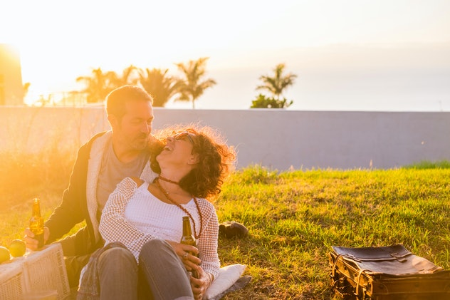 Couple laughing in love during picnic on the meadow for outdoor leisure activity together - married ...