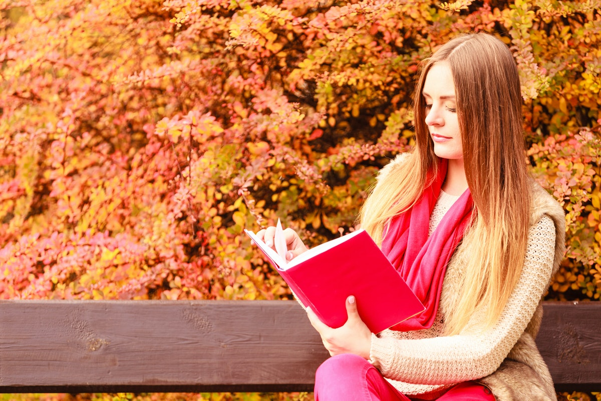 Woman fashion girl relaxing in autumnal park reading book sitting on bench. Fall lifestyle concept.
