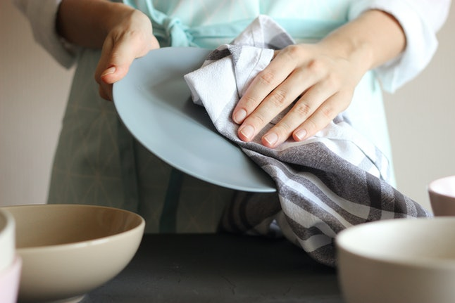 Housewife wipes the dishes with a towel.